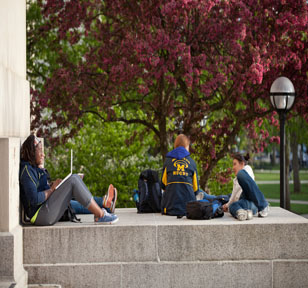 Female students sitting and studying in front of Angell Hall