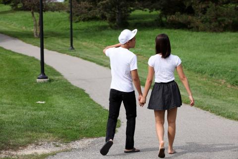 Image of two students walking hand in hand
