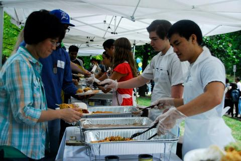 picture of two volunteers serving food to attendees