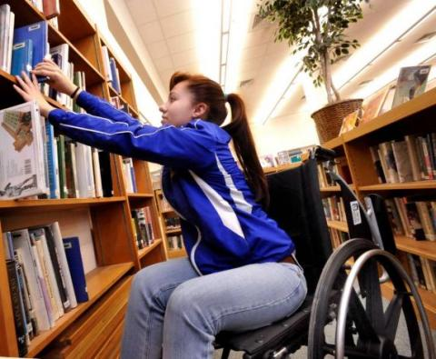 Wheelchair user accessing library bookshelf