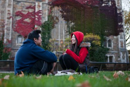 Image of 2 students talking on lawn