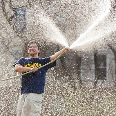 student wearing in U-M t-shirt spraying with a water hose