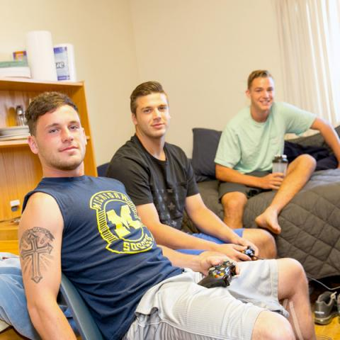 Image of 3 students playing video games in their dorm room