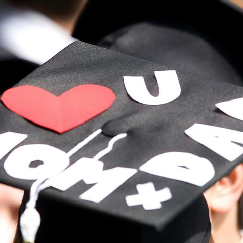 """A graduation cap decorated with """"I love you mom and dad"""" letters."""