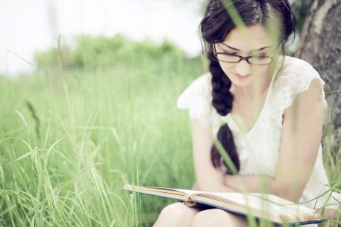 Woman sitting in grassy field, reading a book