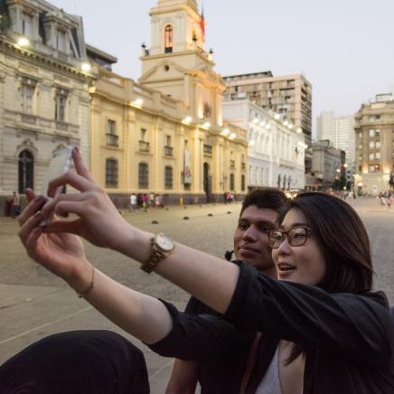 Two University of Michigan students take a selfie picture in a plaza in Santiago