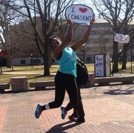 "Student on Diag Holding ""I Heart Consent"" Sign"