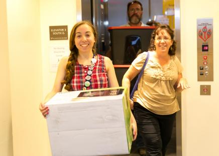 Student moving belongings with parents