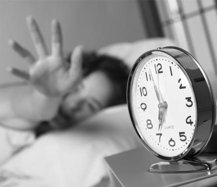 Woman reaching to turn off alarm clock
