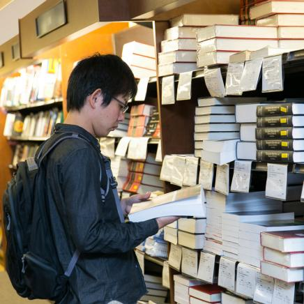 Student looking through stacks of books