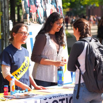 3 students talking at an outdoor student organization fair