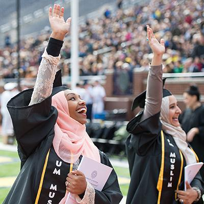 Students wave at the General Commencement ceremony