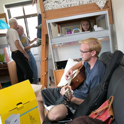 student with guitar and sibling