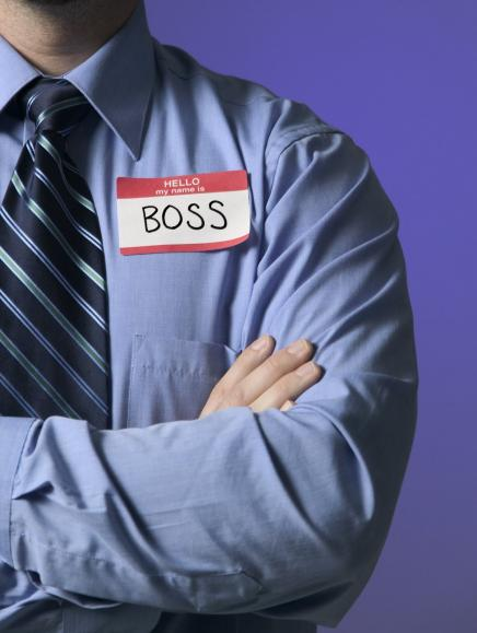 Torso of man wearing a tie, arms crossed, and nametag reading Boss