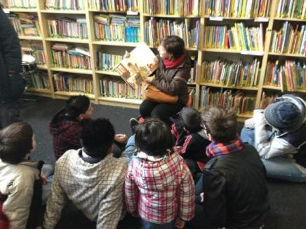 A participant of Alternative Spring Break reads to elementary school students.